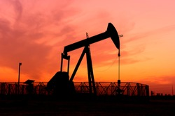 Silhouette of crude oil pump in the oilfield at sunset