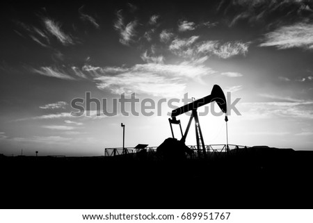 Silhouette of crude oil pump in the oilfield at sunset - Black and white edit