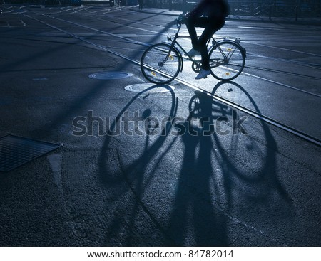 Silhouette of cyclist at sunrise, casting a long shadow