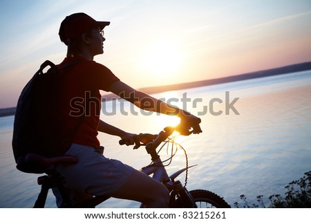 Silhouette of cyclist relaxing on the beautiful sunset