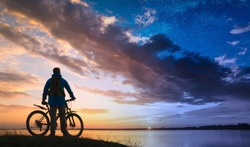 Silhouette of cyclist with bicycle between day and night. Fairytale conceptual landscape.