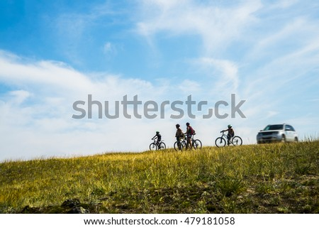 silhouette of cyclist with bikes on blue sunset sky with clouds. Car stand near sporty people. Group of friends or family.  #479181058