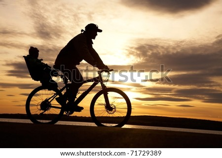 silhouette of cyclist with child in motion on the background of beautiful sunset