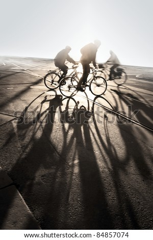 Silhouette of cyclists at sunrise, casting long shadows