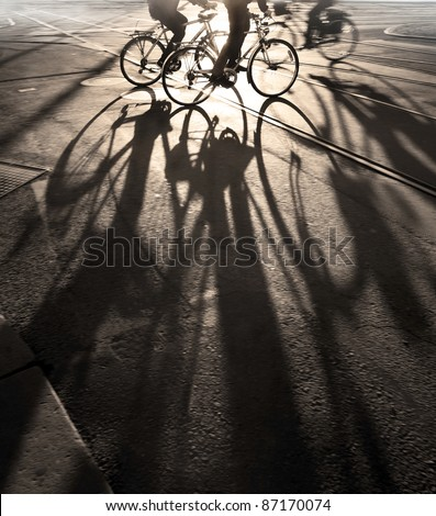 Silhouette of cyclists at sunrise, casting long shadows #87170074