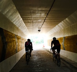 Silhouette of Cyclists in the tunnel