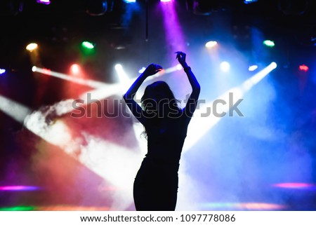 Silhouette of dancing girl against disco lights #1097778086