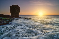 Silhouette of Deil's Heid (Devil's Head) Red sandstone sea stack at Seaton Cliffs during a colourful sunrise at Arbroath east coast of Angus, Scotland.