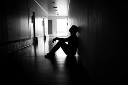 Silhouette of depressed man sitting on walkway of residence building. Sad man, Cry, drama, lonely and unhappy concept.