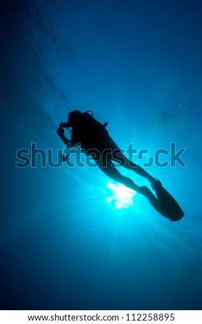 Silhouette of diver with sun disk behind #112258895