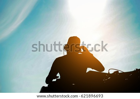 Silhouette of dj mixing outdoor with back sun light - Portrait of disc jockey playing old style vinyl music for people on beach party at sunset - Fun and ,summer,entertainment and fest concept