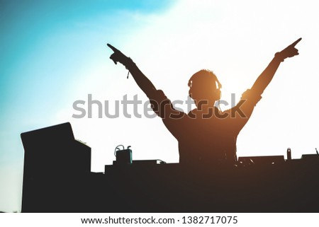Silhouette of dj mixing outdoor with hands up at sunset - Portrait of disc jockey playing old style vinyl music for people on beach party - Fun, summer, entertainment and fest concept - Focus on him