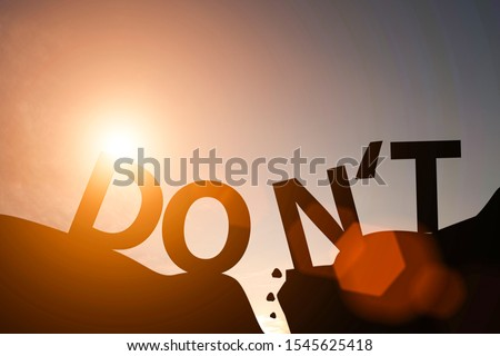 Silhouette of  don't wording and do wording on mountain. Mindset for career growth business.
