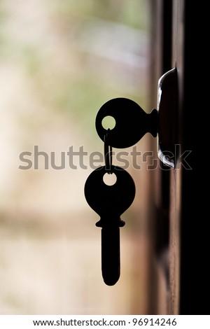 Silhouette of door keys hanging on the open door with blurred background