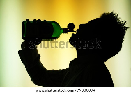 silhouette of drinking  young  man on yellow green  background - back-lighting