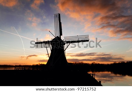 silhouette of Dutch windmill over sky during sunset