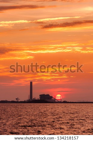 Silhouette of electrical power plant against sunset