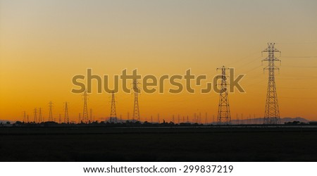 Silhouette of electrical power transmission pylons under sunset golden sky. The photo was taken at Baylands Nature Preserve in Palo Alto, California, by the south end of the San Francisco Bay.