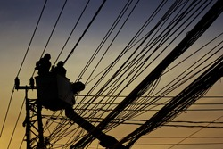 silhouette of electrician and cable
