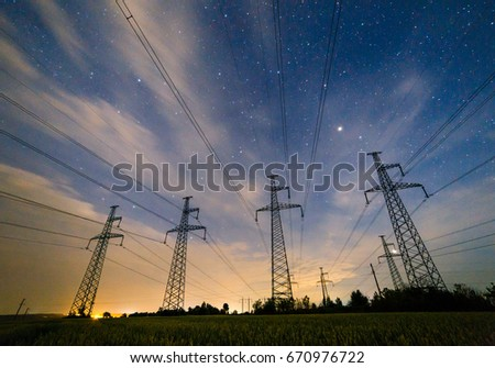 Silhouette of electricity pylons and high-voltage power lines on the wheat field at night. Four electricity pylons in a row on the background of beautiful starry sky with clouds at night. #670976722