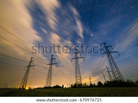 Silhouette of electricity pylons and high-voltage power lines on the wheat field at night. Four electricity pylons in a row on the background of beautiful starry sky with clouds at night. #670976725