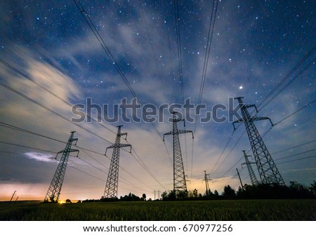 Silhouette of electricity pylons and high-voltage power lines on the wheat field at night. Four electricity pylons on the background of sky with clouds at night. Thunderstorm, lightning in the clouds. #670977256
