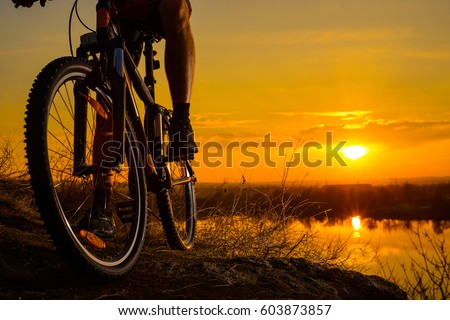 Silhouette of Enduro Cyclist Riding the Mountain Bike on the Rocky Trail at Sunset. Close-up of Bicycle. Active Lifestyle Concept. Free Space for Text.