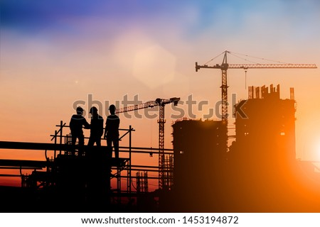 Silhouette of engineer and construction team working at site over blurred background for industry background with Light fair. #1453194872