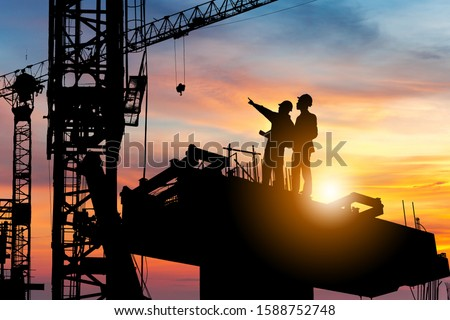 Silhouette of Engineer and worker checking project at building site background, construction site at sunset in evening time.