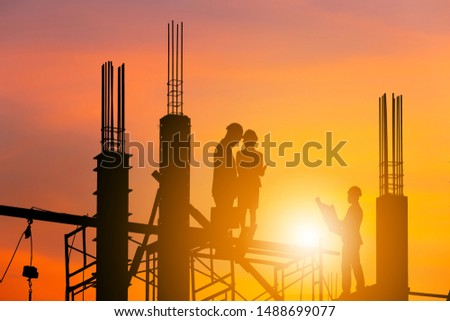 Silhouette of Engineer and worker checking project on building site, construction site at sunset in evening time.