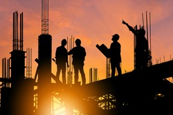 Silhouette of Engineer and worker on building site, construction site at sunset in evening time.