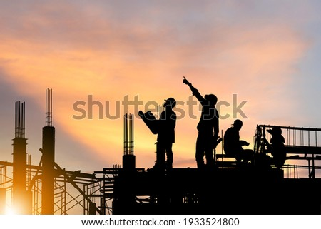 Silhouette of Engineer and worker on building site, construction site at sunset in evening time. Foto stock ©