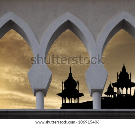 Silhouette of exotic mosque minaret against a surreal fiery sunset sky in an islamic archway for Ramadan fasting month concept.