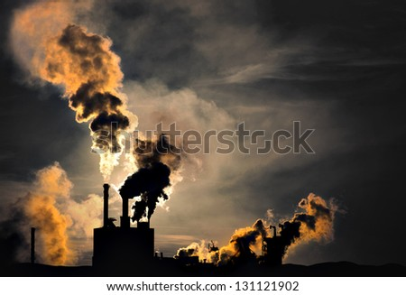 Silhouette of factory with chimneys and heavy smoke