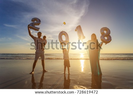 Silhouette of family holding number balloon 2018 on the beach at the sunset time. Outdoor, family and new year concept.