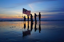 Silhouette of family with waving a Malaysian flag at beach. independence day / merdeka day.