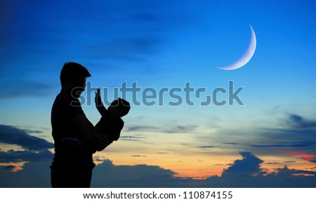 Silhouette of father and child on beautiful summer sunset with half crescent moon - family