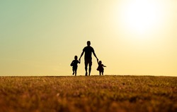 silhouette of father and children holding hands walking outdoors in the park. Fatherhood, and Father's Day concept.