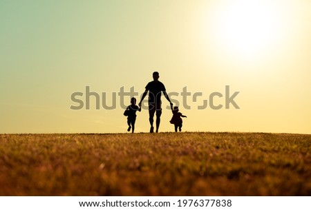 silhouette of father and children holding hands walking outdoors in the park. Fatherhood, and Father's Day concept.  Foto d'archivio ©