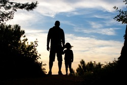 Silhouette of father and daughter holding hands watching the sunset on the top of a forest path
