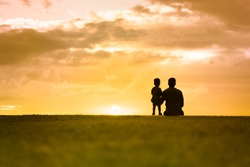 Silhouette of father and his little boy watching the sunset. Childhood, Father's Day concept.