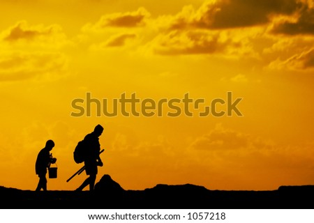 Silhouette of father and son going fishing at sunset