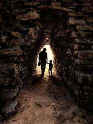 Silhouette of father and son in backlight in a small and dark stone tunnel: Image taken at Tulum in Mexico.