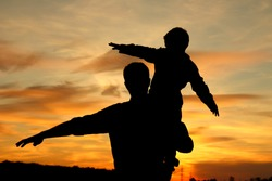 silhouette of father and son play on sunset