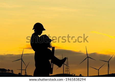 Silhouette of father and son with clipping path in hard hat, Happy dad carrying son on shoulders checking project at wind farm site on sunset in evening time
