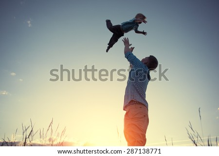 silhouette of father catching his son in the park at sunset (intentional sun glare and vintage color) #287138771