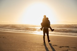 Silhouette Of Father Giving Son Piggyback On Winter Beach