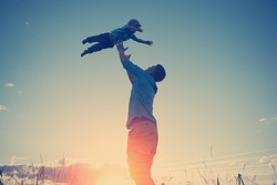 silhouette of father playing with his son in the park outdoors at sunset (intentional sun glare and vintage color)