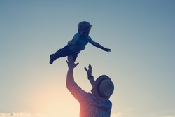 silhouette of father throwing up and catching his son in the park in the evening (intentional sun glare and vintage color, lens focus on father)