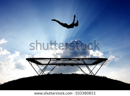 silhouette of female gymnast on trampoline in sky
